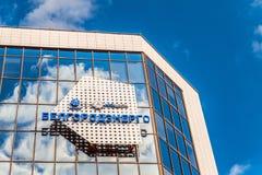 Emblem och logoer på fasad för glass spegel av byggande av Belgorodenergo på en blå molnig bakgrund Belgorod Ryssland Fotografering för Bildbyråer