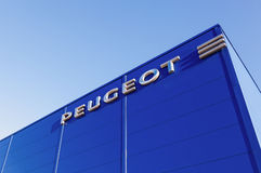 The emblem Peugeot on the building of official dealer. Stock Photo