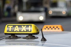 Emblem taxi by car. Automobile emblem and sign of a taxi against city streets with the vague image of buses and the included headlights Royalty Free Stock Image