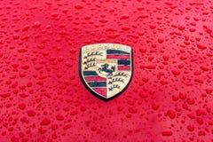 Emblema da capa do carro de esportes Porsche nos pingos de chuva no fundo vermelho Imagens de Stock Royalty Free