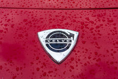 Emblema da capa do carro de esportes Volvo P1800 nos pingos de chuva no fundo vermelho Fotografia de Stock