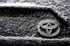 Emblema do carro coberto com as grões da neve branca imagens de stock