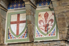 Emblems on the facade of the Palazzo Vecchio in Florence. Detail of two emblems of the Florentine Republic on the facade of the Palazzo Vecchio in Florence Stock Photo