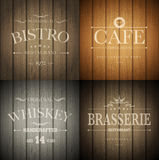 Emblems on wood texture. Bistro, cafe, brasserie and whiskey emblem templates on wooden background. Vector illustration Stock Images