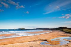 Embleton Burn snakes across Embleton Beach. Embleton Bay is a wide sandy beach with the ruins of Dunstanburgh Castle providing a stunning backdrop,located on the stock photo