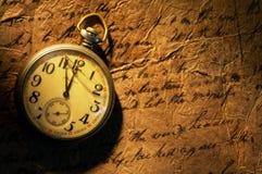 Embolse el reloj en el papel viejo Imagen de archivo libre de regalías