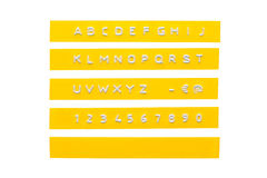 Embossed alphabet on yellow plastic tape Royalty Free Stock Images