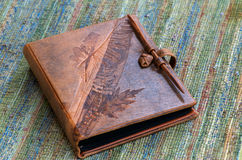 Embossed Leather Book. Elegant leather book (photo album, journal or scrapbook) with brown embossed leaf pattern Royalty Free Stock Photo