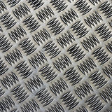 Embossed steel cover. A grubby embossed stainless steel pavement cover Stock Photos