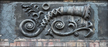 Embossed three-dimensional image on the wall of an old house above the brickwork: long curved pipe in the form of a shell, flowers Royalty Free Stock Images