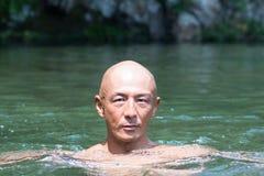 Embote al individuo japonés de la cabeza calva empapado en el río imágenes de archivo libres de regalías