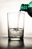 Embotelle el agua de colada en un vidrio Imagenes de archivo