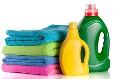 Embotelle el detergente para ropa y el acondicionador con las toallas aisladas en el fondo blanco Foto de archivo