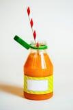 Embotelle el smoothie anaranjado con la paja en el fondo blanco Fotografía de archivo