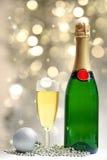 Embotelle y un vidrio de champán con las decoraciones de la Navidad Foto de archivo libre de regalías