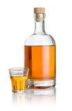 Embotelle y vaso de medida biselado llenado del líquido ambarino Fotografía de archivo