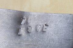 Embouti POUR AIMER l'inscription en métal L'inscription sur le métal p Image stock