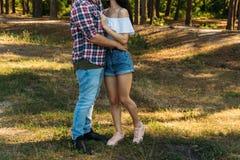 embrace Amor e afeição entre um par novo no parque um indivíduo em um plano e calças de brim da manta, uma menina no short e um j imagens de stock royalty free