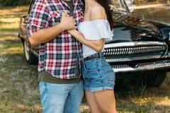 embrace Amor e afeição entre um par novo no parque, perto do carro velho um indivíduo em um plano da manta e nas calças de brim,  imagem de stock royalty free