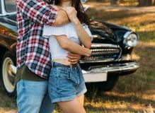 embrace Amor e afeição entre um par novo no parque, perto do carro velho um indivíduo em um plano da manta e nas calças de brim,  fotografia de stock