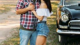 embrace Amor e afeição entre um par novo no parque, perto do carro velho um indivíduo em um plano da manta e nas calças de brim,  foto de stock royalty free