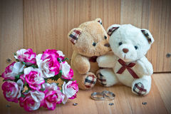 Embrace Bears in love, sit near bouquet rose and ring. Royalty Free Stock Images