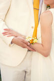 Embrace the bride and groom. Bride with yellow bracelet on her arm hugging the bride in a light suit Royalty Free Stock Photo