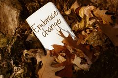 Embrace Change Words Written on Card in Autumn Leaves. Learning how to embrace change and challenge to innovate and succeed Royalty Free Stock Photo