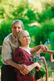 Embrace and kiss of old couple in a park on a sunny day. stock photo