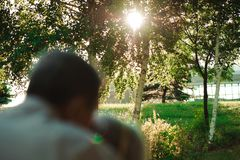 Embrace and kiss of old couple in a park on a sunny day royalty free stock photo