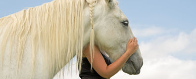Embrace. Owner standing to the side of her horse with protective arm embrace Stock Image