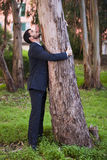 Embrace a tree trunk. Businessman embrace a tree trunk Stock Photo