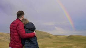 Embraced boy and girl couple of lovers admiring the beautiful landscape with hills and rainbow -. Embraced boy and girl couple of lovers admiring the beautiful stock video