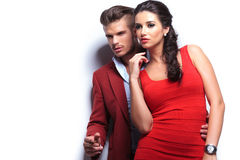 Embraced fashion couple leaning against white wall Royalty Free Stock Photos