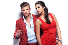 Embraced fashion couple leaning against white wall Royalty Free Stock Images