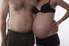 Embraced fat couple. Embraced pregnant women and fat men on white background Stock Images