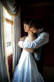 Embraced kiss. Groom kissing bride at her shoulder from the  back Stock Image