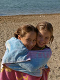 Embraced sisters on beach Royalty Free Stock Photos