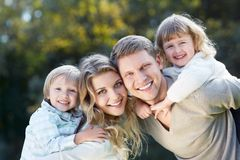 Embraces family. Smiling family with children outdoors Stock Image