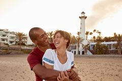 Embracing adult couple posing on beach. Loving adult couple posing on the beach in an embrace with toothy smiles of happiness and looking at each other stock image