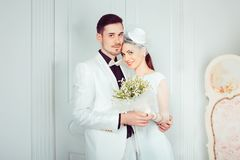 Embracing beautiful newlyweds in elegant interior stock photography