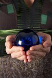 Embracing blue magic ball. Woman hand detail with a blue ball on her palm Stock Photos
