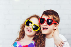 Embracing boy and girl with sunglassec heart shape.  Happy tooth Royalty Free Stock Photography