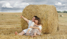 Embracing couple admire beautiful nature in summer. Young happy embracing couple admire beautiful nature in summer field stock photos