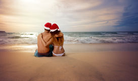 Embracing couple looking sunset with Christmas hat Stock Photo