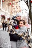 Embracing couple under the blanket plaid looking at camera with smiles. New year and Christmas eve royalty free stock photo