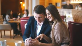 Embracing couple using mobile phone in cafe. Young smiling guy and girl , watching a movie on mobile phone while sitting at cafe and drinking coffee stock footage