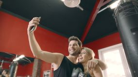 Embracing fitness couple posing to mobile phone for selfie in gym club. Sport man taking selfie photo woman boxer together. Happy people making selfie picture stock video