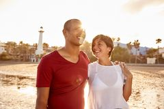 Embracing loving adult couple on beach. Embracing happy loving adult couple walking along the beach with their arms around each other and hands interlocked in Royalty Free Stock Image
