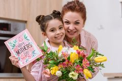 Embracing mother and daughter with mothers day greeting card. And bouquet stock photos